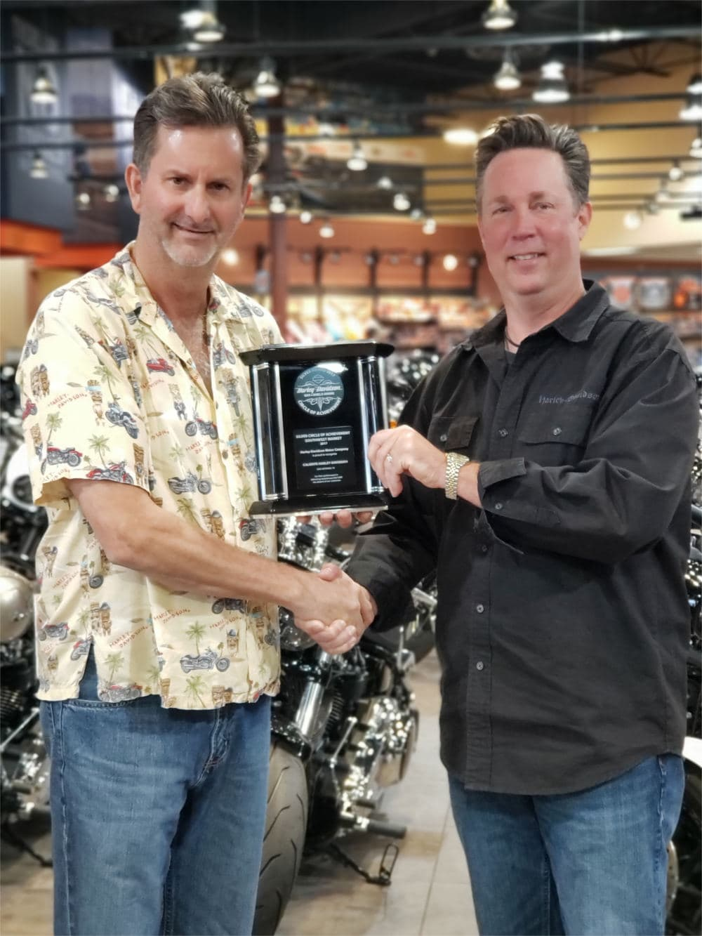 A staff-member receives the Harley-Davidson Bar and Shield award plaque.