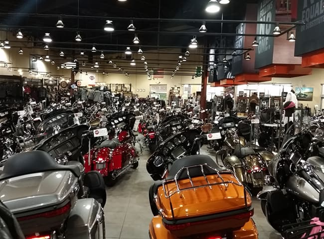 Rows of motorcycles on the large showroom floor of the dealership.